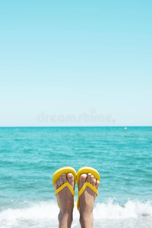 Man upside down wearing flip-flops on the beach. Closeup of the legs of a young caucasian man on the beach, upside down, wearing a pair of yellow flip-flops stock photo