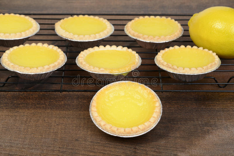 Closeup lemon tart with more cooling on rack stock photo