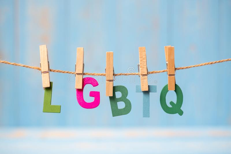 Closeup LGBTQ text, for lesbian, gay, bisexual, transgender, and hanging on line with blue wooden background stock photography