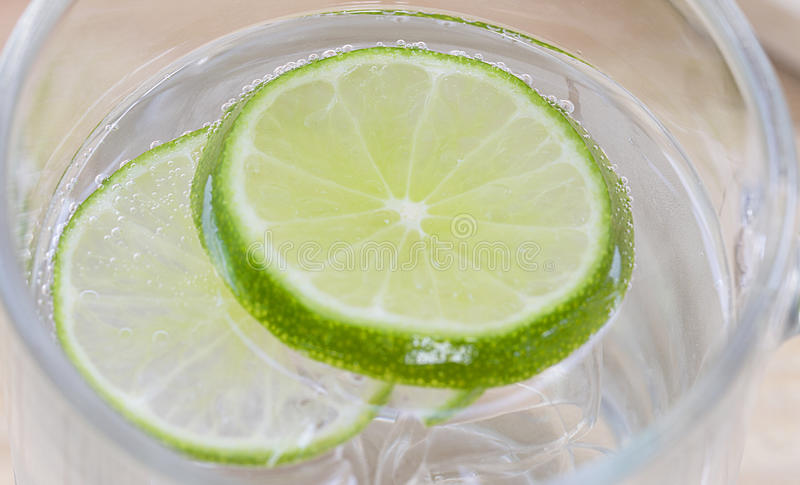 Closeup lime in glass of soda stock photography