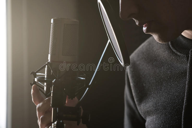 Closeup of lips and hands on a microphone of a young man standing in profile in the rays of the sun. Horizontal photo stock photography