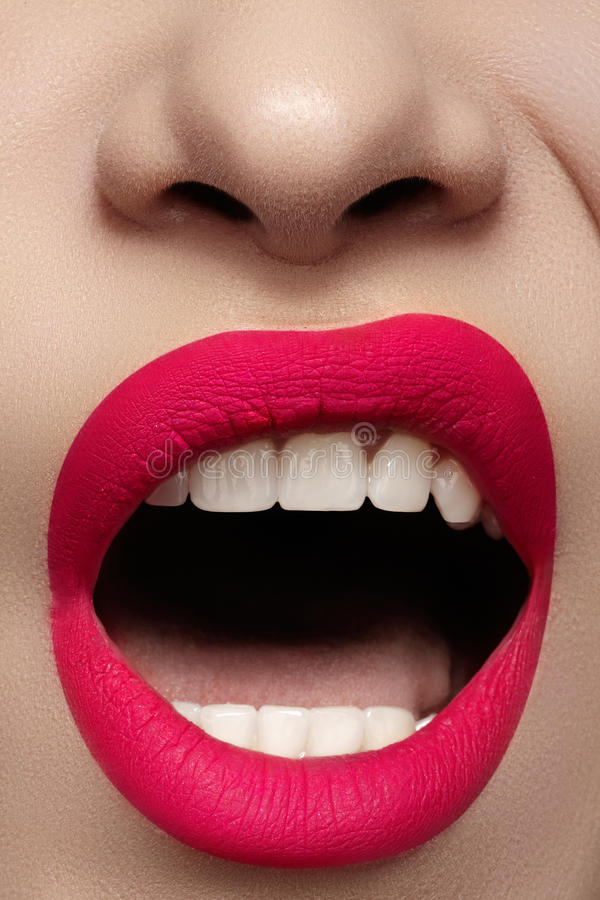 Closeup of lips makeup. Beautiful fashion bright pink lip mat make-up. Macro glamour fashion bright pink lip mat make-up. Close-up shot of kissable taste female royalty free stock image