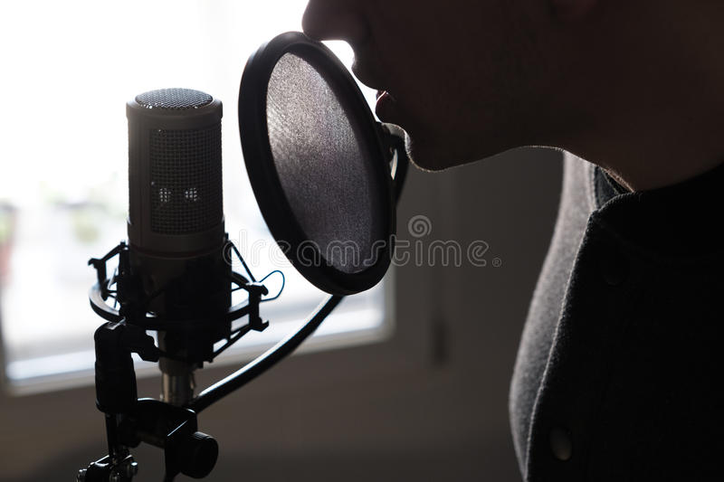 A closeup of lips at the microphone of a young man standing in profile. Horizontal photo stock image