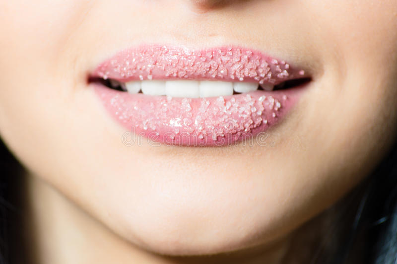 Closeup on lips of young woman in sugar pleasantly softly smiling white teeth stock image