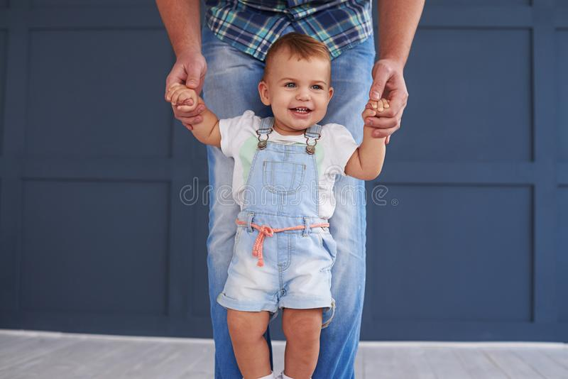 Little baby girl doing her first steps with father stock photos