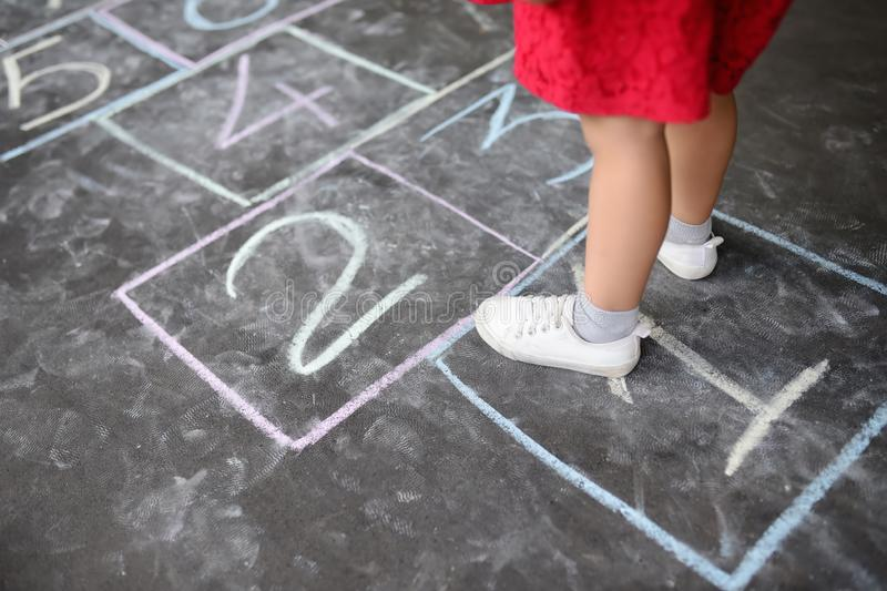 Closeup of little girl`s legs and hopscotch drawn on asphalt. Child playing hopscotch game on playground outdoors on a sunny day. Summer activities for stock images