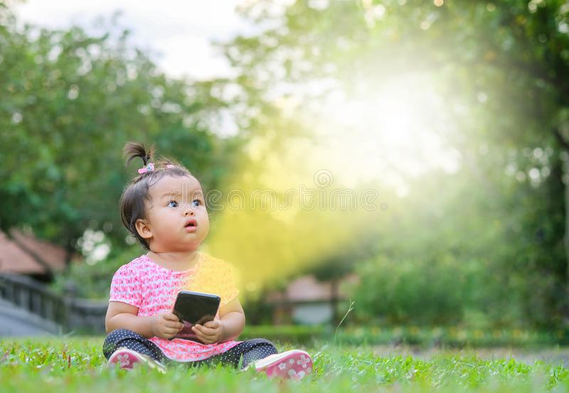 Closeup little girl sit on grass floor and look at space like a text box caused by light from mobile phone on park view background royalty free stock photography