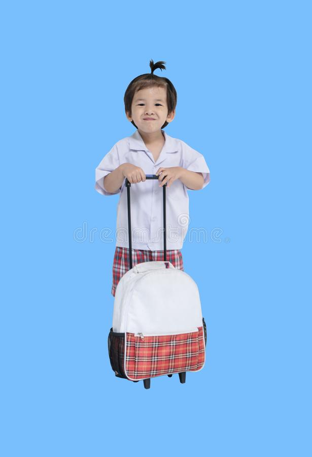 Closeup a little kid in student uniform with schoolbag isolated on blue background. Closeup a kid in student uniform with schoolbag isolated on blue background royalty free stock photography