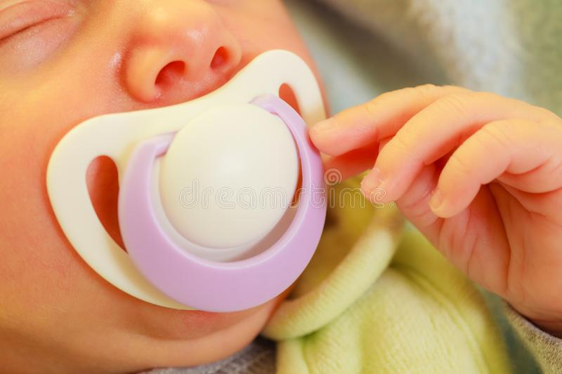 Closeup of little newborn sleeping with teat in mouth stock photos
