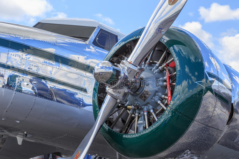 Closeup of Lockheed Electra Polished Fuselage. Outdoor photo of a vintage Lockheed Electra with green trimmed engine cowling and polished fuselage royalty free stock photography