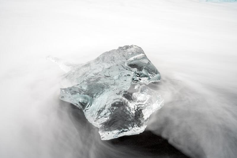 Closeup and long exposure shot of clear ice chunk on black lava beach in Iceland. Global warming, traveling and pollution concept royalty free stock photography