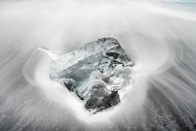 Closeup and long exposure shot of clear ice chunk on black lava beach in Iceland. Global warming, traveling and pollution concept stock images