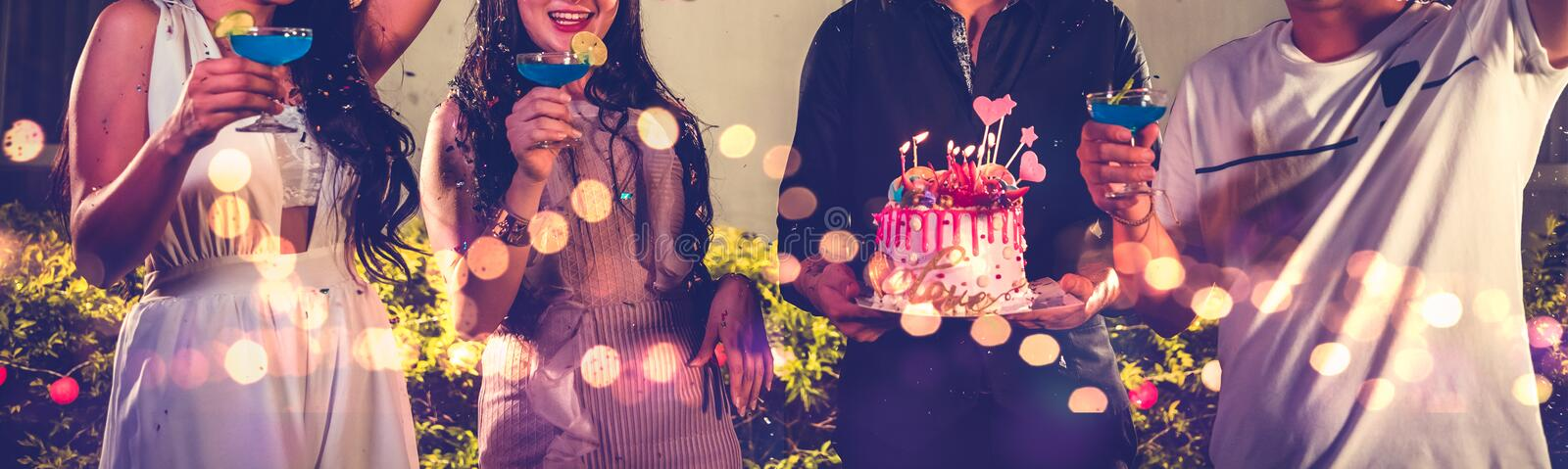 Closeup lower body friends group having outdoor birthday party at night club with birthday cake. Event and anniversary concept. royalty free stock image