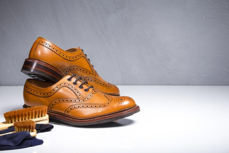 Closeup of Luxury Male Tanned Full Broggued Oxford Calf Leather. Shoes Along with Cleaning Accessories and Cloth.Horizontal Image stock photo