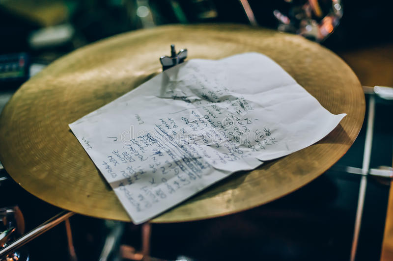 Closeup of lyrics paper with a song text lying on drum set. Musician equipment detail royalty free stock photography