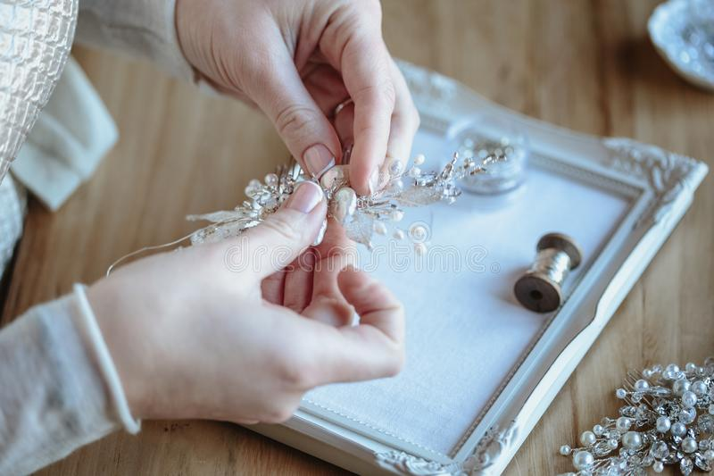 Closeup macro photo of details, workplace of decorator and creator of wedding imitation jewelry. Woman`s hands in a process of creation royalty free stock photos