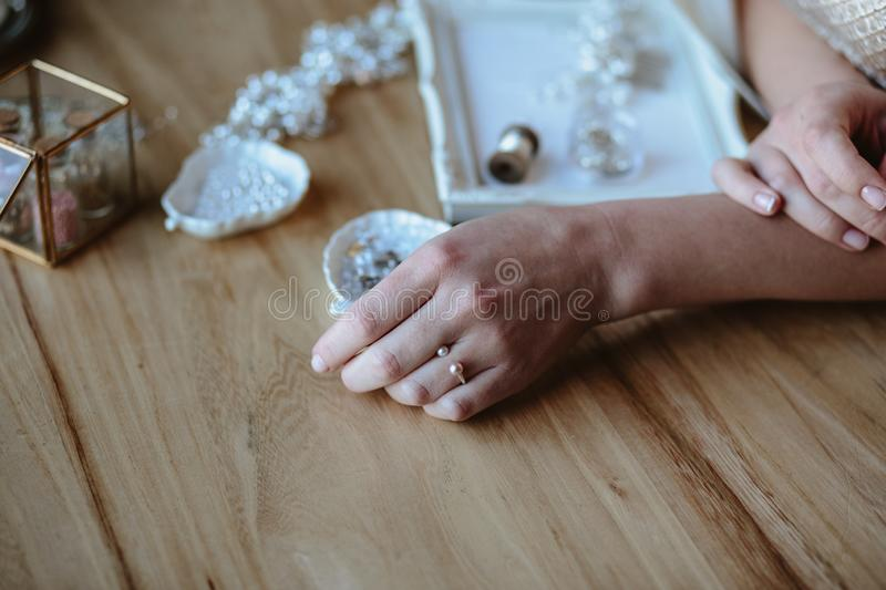 Closeup macro photo of details, workplace of decorator and creator of wedding imitation jewelry. Woman`s hands in a process of creation royalty free stock image