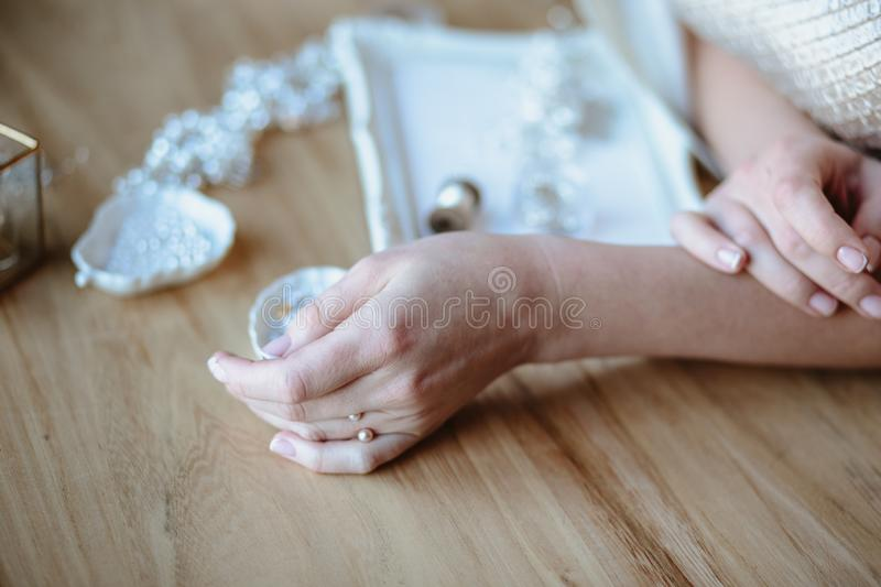 Closeup macro photo of details, workplace of decorator and creator of wedding imitation jewelry. Woman`s hands in a process of creation stock photos