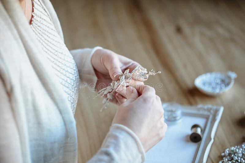 Closeup macro photo of details, workplace of decorator and creator of wedding imitation jewelry. Woman`s hands in a process of creation royalty free stock images