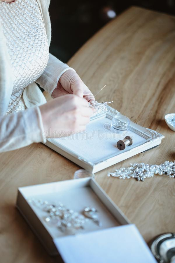 Closeup macro photo of details, workplace of decorator and creator of wedding imitation jewelry. Woman`s hands in a process of creation stock photography