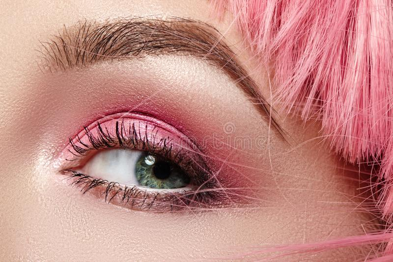 Closeup Macro of Pink Fashion Eye Make-up. Expressive Makeup, Bright Summer Eyeshadows, Magenta Color Hair, Shiny Skin stock photo