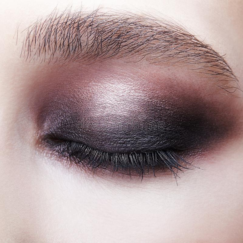 Closeup macro portrait of closed human female eye. Girl with perfect violet - black smoky eyes make-up royalty free stock photo