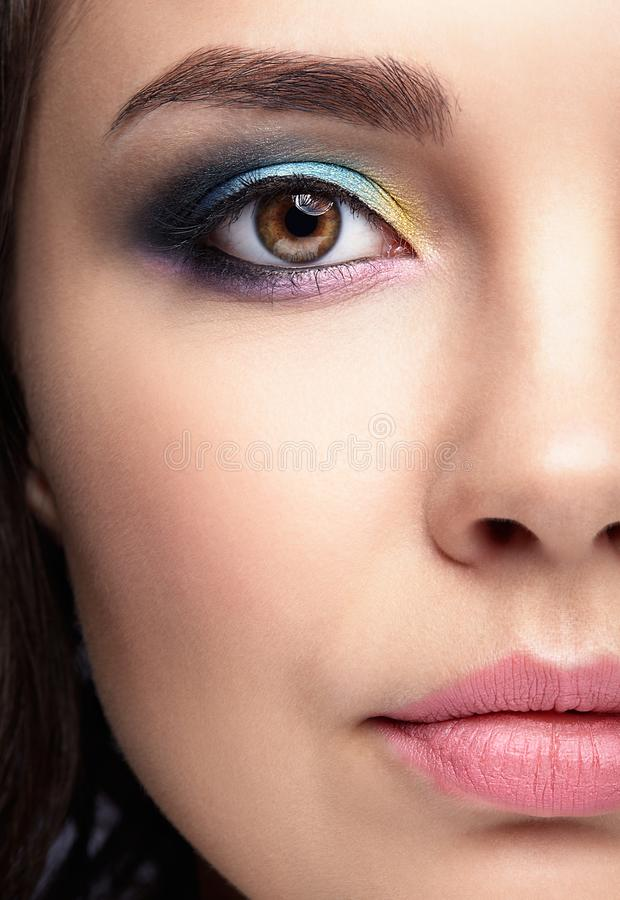 Closeup macro portrait of female face. Human woman half-face wi. Th evening beauty makeup. Girl with perfect skin and yellow - blue eye shadows royalty free stock photos