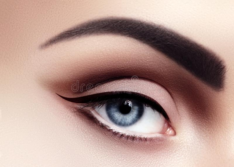 Closeup Macro of Sexy Woman Eyes with Evening Fashion Make-up. Black Liner and Strong Brows. Retro Diva Style Eye Makeup stock images