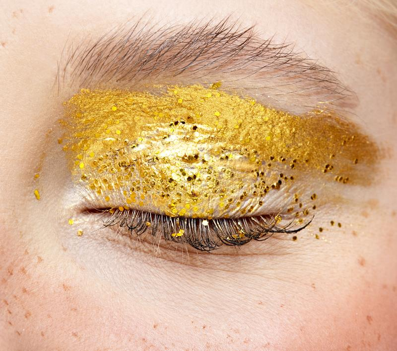 Closeup macro shot of closed human female eye with yellow smoky eyes beauty makeup stock images