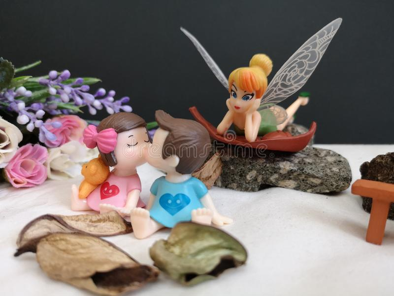 Closeup and macro shot of miniature kissing babies in the garden while fairy Tinkerbell stalking behind.. royalty free stock photo