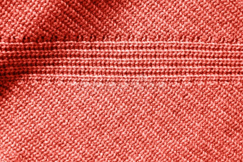 Closeup macro texture of knitted cotton waffle fabric in a color of the year 2019 Living Coral Pantone. stock photos