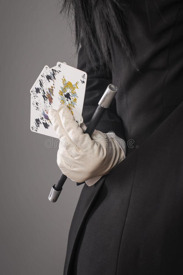 Magic wand and cards in hands of female magician. Closeup royalty free stock images
