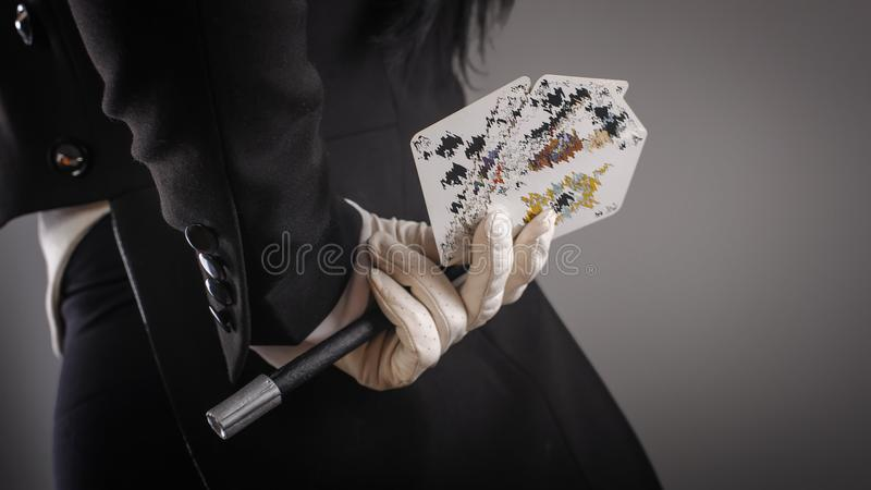 Magic wand and cards in hands of female magician. Closeup royalty free stock image