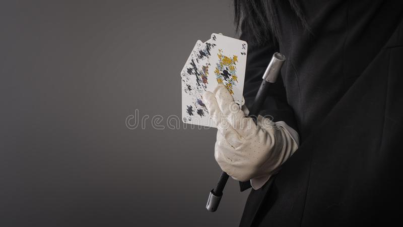 Magic wand and cards in hands of female magician. Closeup stock photo