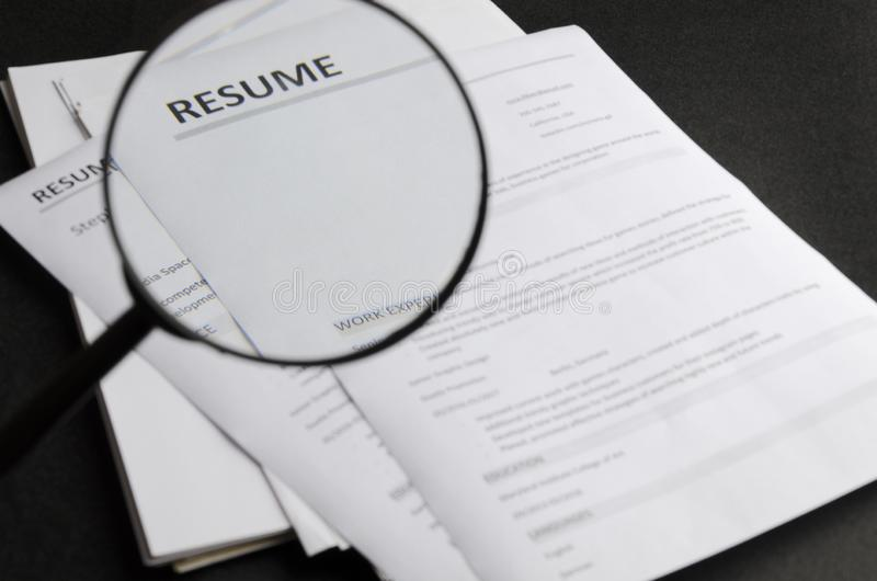 Closeup of magnifier, looking through the magnifier while reviewing new candidate`s resume applictaions.Concept of searching royalty free stock images