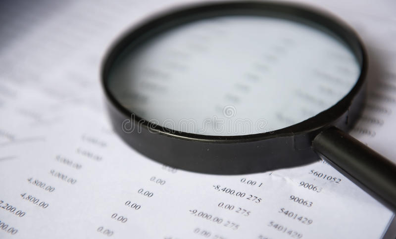 Closeup magnifying glass with finance business sheet royalty free stock photos
