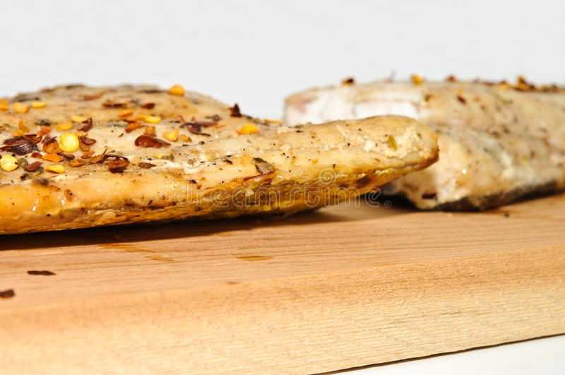 Closeup of Mahi-Mahi on Wooden Plank. Closeup of a piece of grilled Mahi on a plank royalty free stock photo