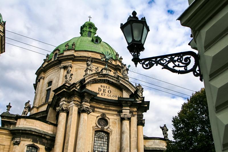 Closeup Facade of Old Dominic Cathedral Streetlamp. Closeup main facade of age-old Dominic Oder cathedral at foreground streetlight in old european city royalty free stock photo
