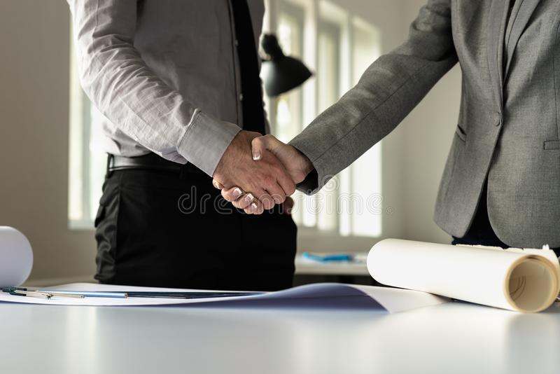 Closeup of male and female business partners shaking hands stock photo