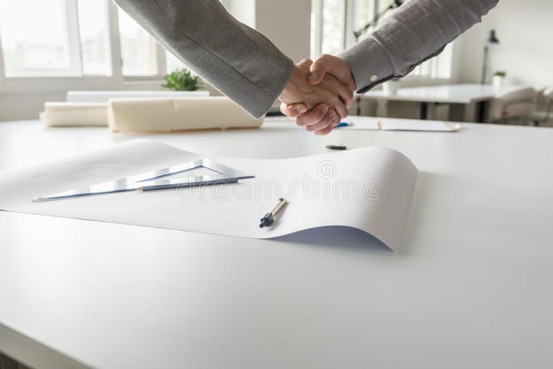 Closeup of male and female business partners shaking hands stock image