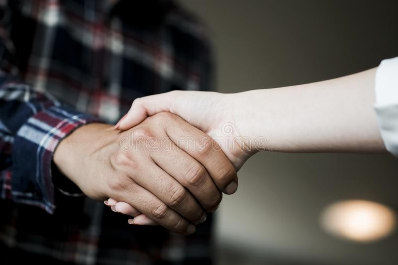 Closeup of male and female hands handshaking after effective negotiation showing mutual respect. Two people handshaking expressing stock photo