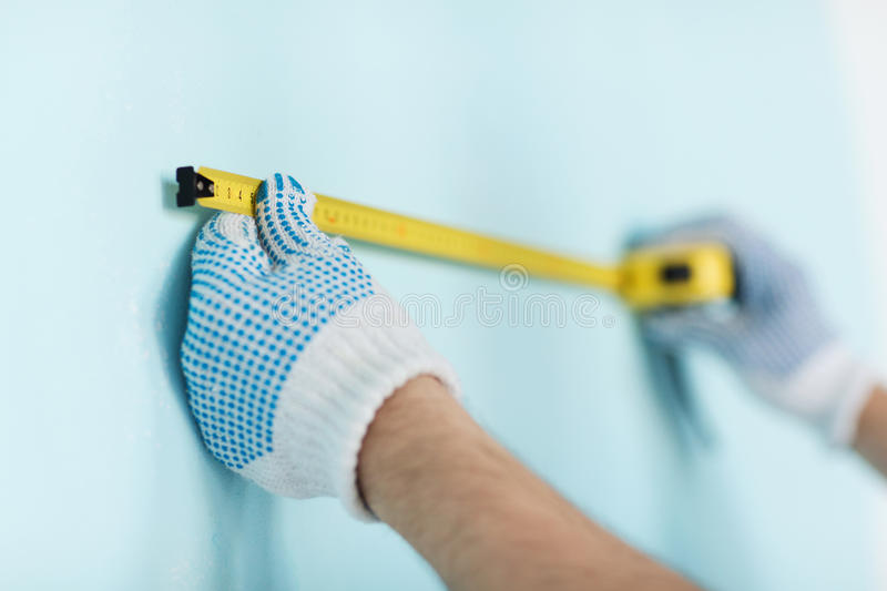 Closeup of male in gloves measuring wall with tape royalty free stock photography