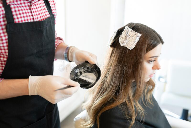 Woman Getting Hair Dyed From Hairdresser At Salon. Closeup of male hairdresser mixing dye while applying on hair of female client stock photo