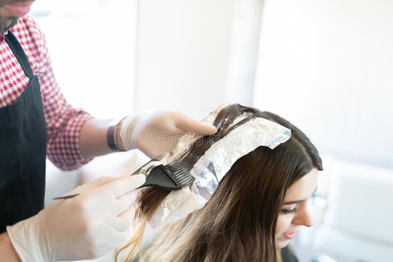 Hairdresser Dyeing Hair Of Female Client. Closeup of male hairstylist applying dye on hair of women with brush at salon stock image