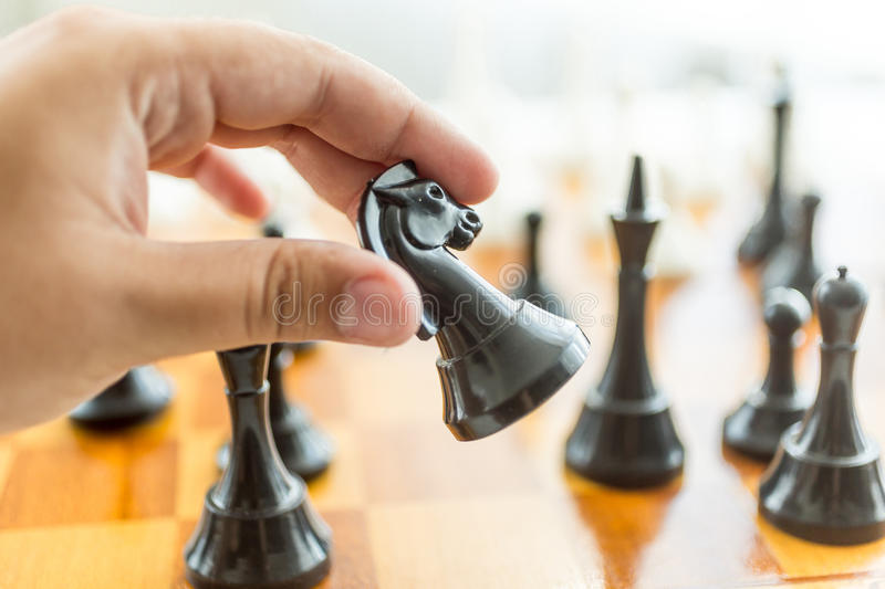 Closeup of male hand holding black horse chess piece. Closeup photo of male hand holding black horse chess piece royalty free stock photography