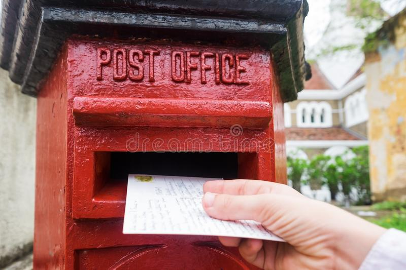 Closeup on a male hand putting a letter in a red letterbox. Concept of vintage type of communication. royalty free stock photo