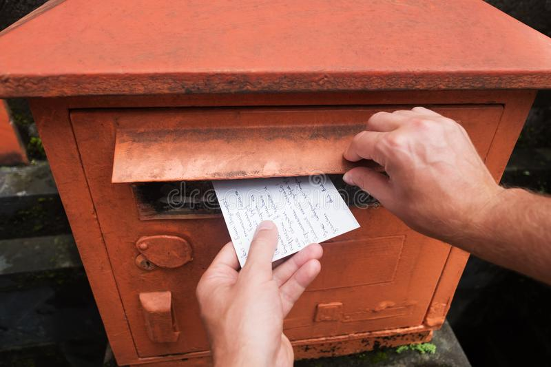 Closeup on a male hand putting a letter in a red letterbox. Concept of vintage type of communication. stock photo