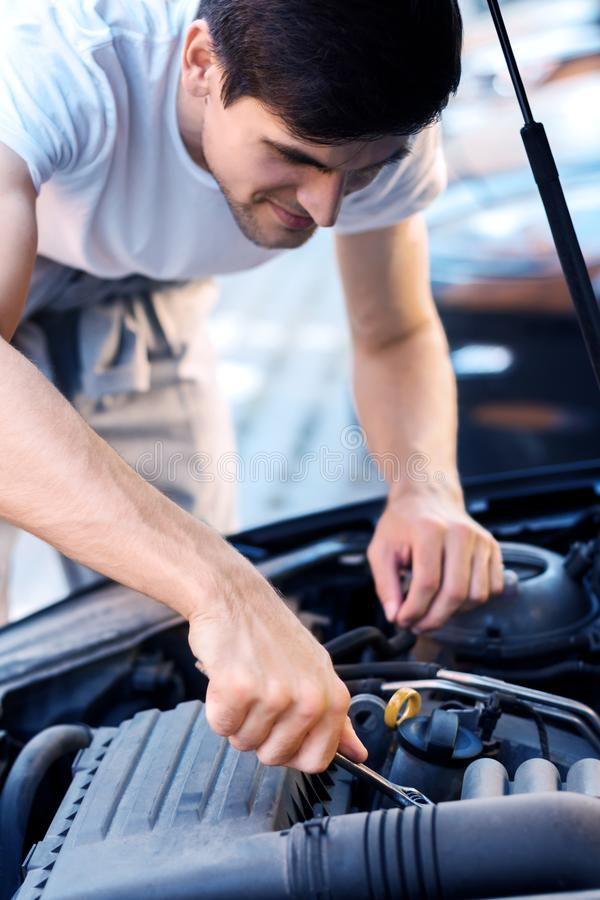 Young driver repairing cars engine in street. Closeup male hands with metal .wrench are tightening nuts in auto with open hood. Young man driver is repairing stock photos
