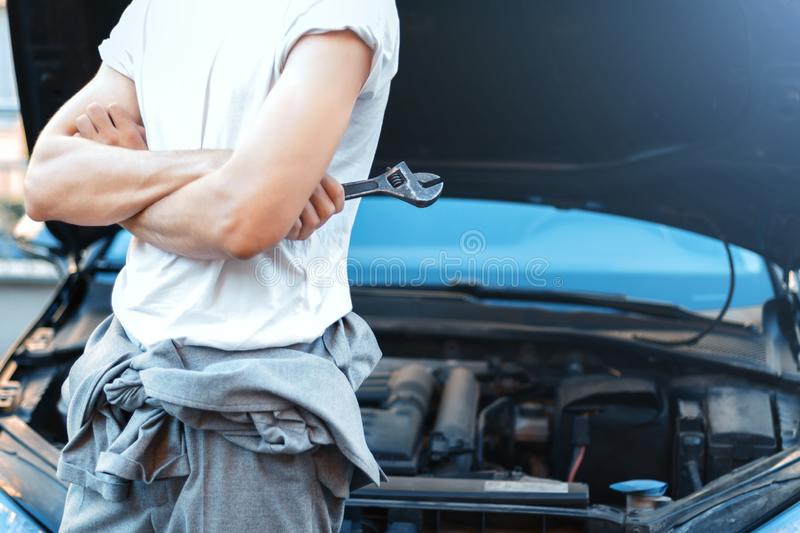 Young driver repairing cars engine in street. Closeup male hands with metal .wrench for tightening nuts. Car with open hood on background. Young man repairman stock photos