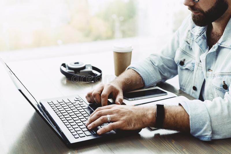 Closeup of male hands typing on computer keyboard. Bearded man uses laptop in cafe. Businessman working remotely royalty free stock images